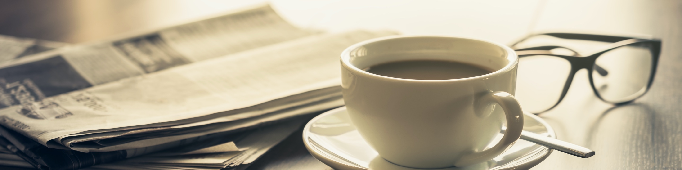 Cup of coffee next to a newspaper and a pair of glasses